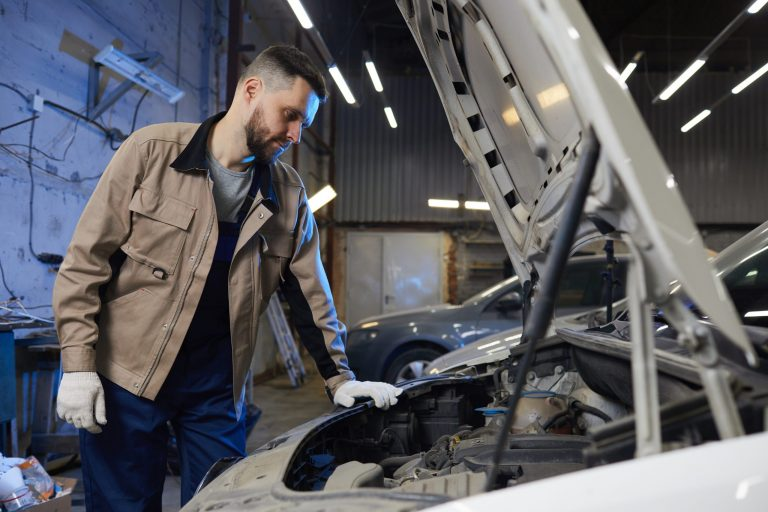 Horizontal medium long shot of professional auto mechanic wearing uniform looking at car motor, copy space